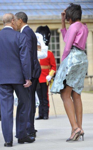 Bahkan ibu negara Michelle Obama pun harus berjuang melawan angin kencang saat sedang berkunjung ke istana Buckingham, London