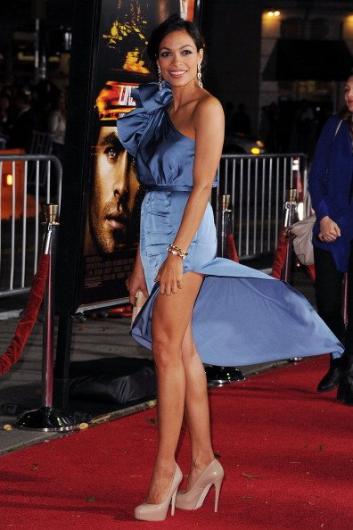 Untung belahan rok Rosario Dawson tak terlalu tinggi sehingga rok hanya tersingkap angin hingga paha